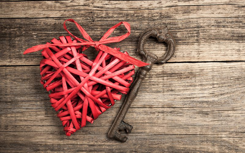 Red wicker heart and vintage key on wooden background